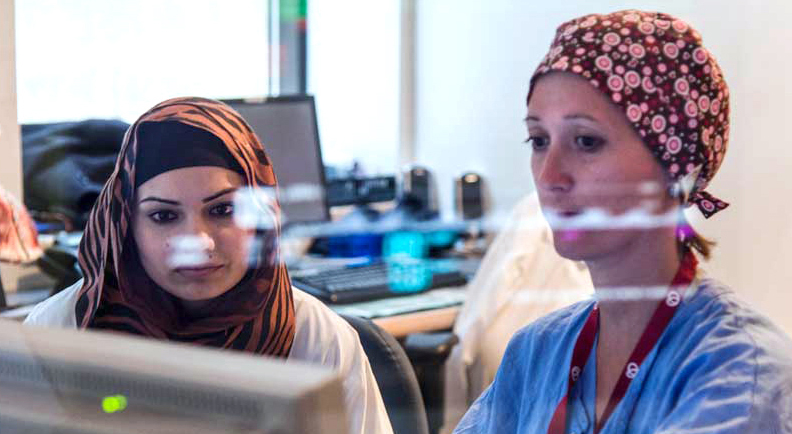 Two nurses sitting in the control room during a procedure monitoring via screen