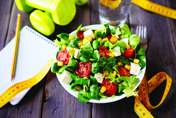 Photo of healthy salad, measuring tape to measure body, glass of water and fitness weights