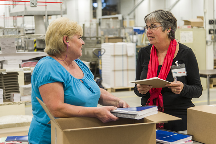 Heart Institute vocational counsellor Laura Cupper (right) often travels to work sites to assess job-related demands that could pose problems for heart disease patients. Here she observes bindery worker Maureen Lafontaine at a printing facility of the Lowe-Martin Group.