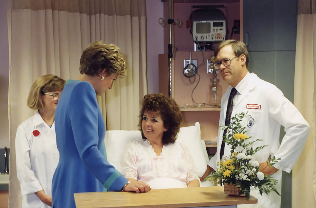 Princess Diana and Dr. James Robblee visit with a patient.