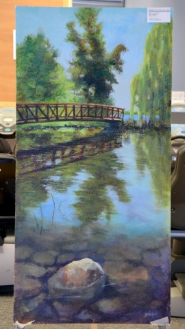 Those familiar with Ottawa may recognize the location in the painting donated by Bev Legault. It's a scene of the Dominion Arboretum. Bev said she took more than 150 photographs of the area to help create the serene scene shown here.