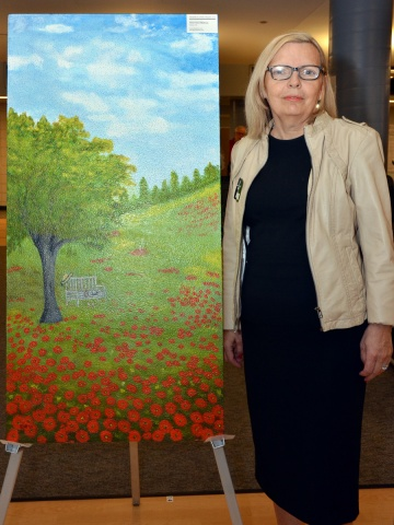 """""""Tranquility in a Field of Poppies,"""" a painting by Eleni Helen Mallinos, is based on a real place in Eleni's hometown, Florina, Greece. Eleni moved to Canada when she was eleven, and now works as a full-time artist. Eleni said, """"Poppies are my peaceful place. This piece makes me smile. If I can help bring a smile to somebody else, then it's all worth it."""""""