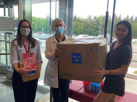 UOHI employees pose for a picture while accepting a donation of masks.
