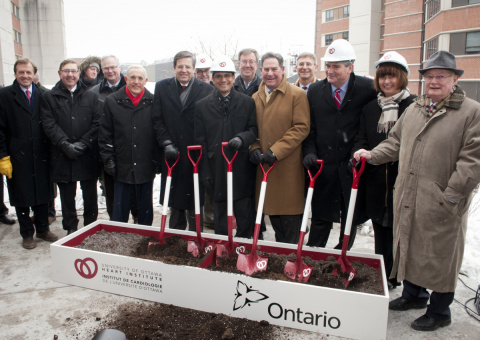 Political dignitaries and institutional leaders pose for a picture at an official groundbreaking ceremony.