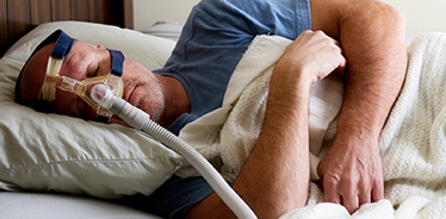 Man wearing continuous positive airway pressure (CPAP) machine to treat sleep apnea