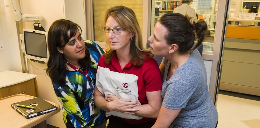Heart Institute occupational therapist Linda Varas Brulé (left) offers skills training for caregivers, such as how to safely help a patient stand up without risking injury to them or their caregiver.