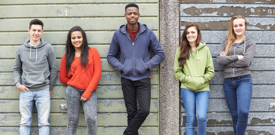 Five teenagers leaning against a wall