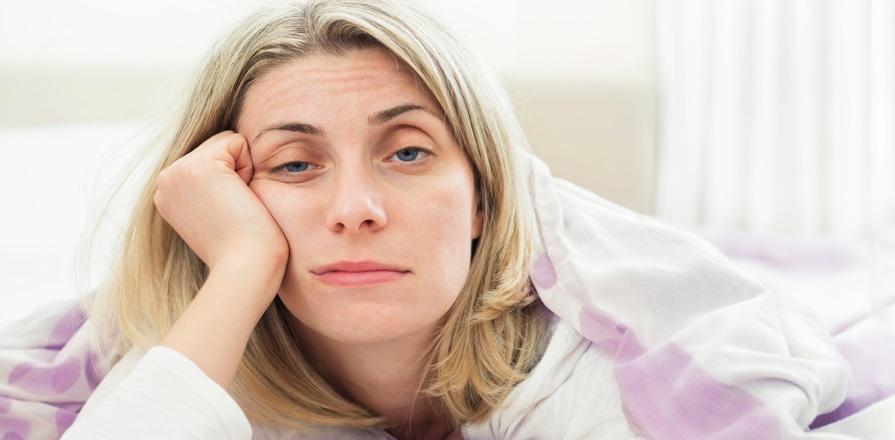 Une femme endormie retient sa tête avec sa main droite.