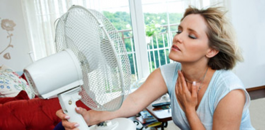 A woman cooling off in front of fan.
