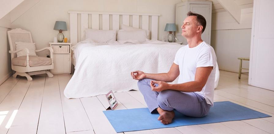 Un homme en méditation dans une chambre à coucher