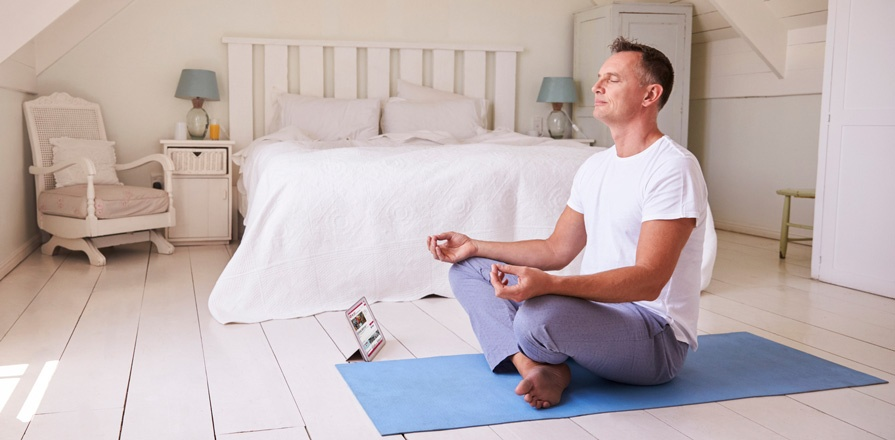 A man meditating in his bedroom