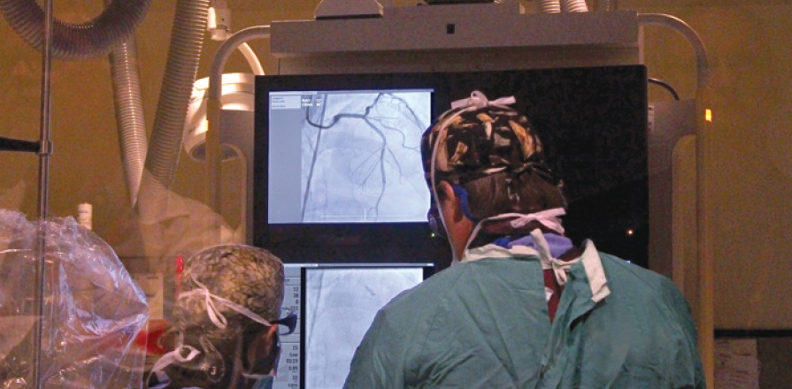 Participants in the ENACT-AMI trial undergo cardiac catheterization in which genetically altered stem cells, unaltered stem cells or a placebo is injected directly into the coronary artery near the damaged tissue. Heart Institute cardiologist Dr. Sandy Dick (right) performs the procedure on the trial's first participant.