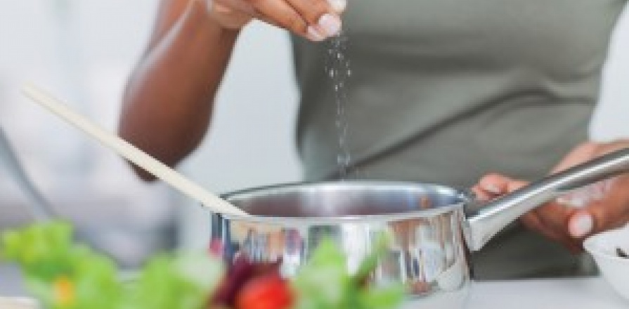 A woman adding salt to a dish